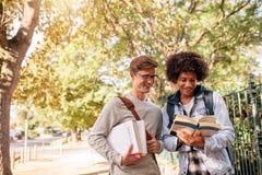Livro de leitura das estudantes universitário no terreno da faculdade Fotografia de Stock Royalty Free