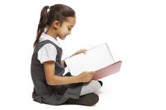 Livro de leitura de assento da menina da escola Foto de Stock Royalty Free