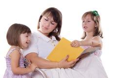 Livro de leitura de escuta da mãe de duas filhas Fotos de Stock Royalty Free