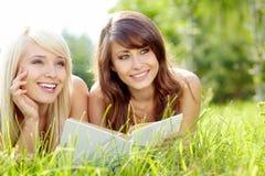 Livro de leitura de sorriso bonito novo de duas mulheres Imagens de Stock Royalty Free