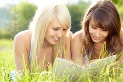 Livro de leitura de sorriso bonito novo de duas mulheres Fotografia de Stock