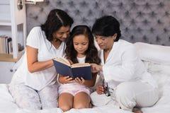 Livro de leitura de sorriso da família da multi-geração ao sentar-se na cama Fotografia de Stock Royalty Free