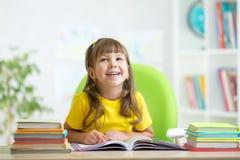 Livro de leitura de sorriso da menina da criança em casa Foto de Stock