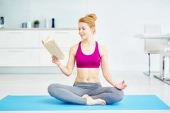 Livro de leitura de sorriso da mulher do iogue Foto de Stock Royalty Free