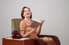 Livro de leitura de sorriso da mulher Imagens de Stock Royalty Free