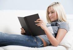 Livro de leitura de sorriso da mulher no sofá imagem de stock