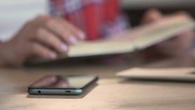 Livro de leitura Defocused da pessoa no café, apreciando o lazer, smartphone na tabela filme