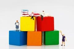 Livro de leitura diminuto com blocos de madeira coloridos, educ dos povos imagem de stock