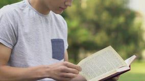 Livro de leitura do adolescente fora, preparando-se a passar o exame, estudante diligente filme