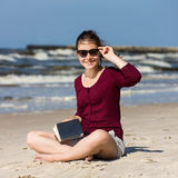 Livro de leitura do adolescente que senta-se na praia Foto de Stock
