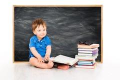 Livro de leitura do bebê perto do quadro-negro, crianças adiantadas educação, criança imagens de stock