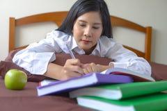 Livro de leitura do concentrado da jovem mulher conce da avaliação da educação imagem de stock