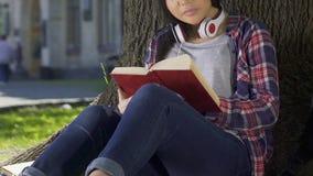 Livro de leitura do estudante fêmea tomado da biblioteca da universidade, fazendo seus trabalhos de casa filme