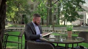 Livro de leitura do homem de negócios durante a ruptura do coffe outdoor tiro do steadicam filme