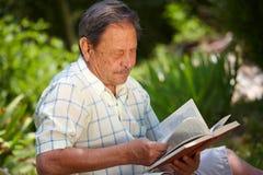 Livro de leitura do homem idoso Imagens de Stock Royalty Free