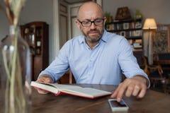 Livro de leitura do homem interno e que usa o telefone Fotografia de Stock Royalty Free