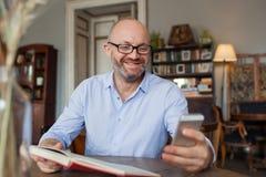 Livro de leitura do homem interno e que usa o telefone Imagem de Stock Royalty Free