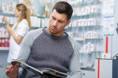 Livro de leitura do homem na farmácia fotografia de stock