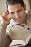 Livro de leitura do homem novo em casa Fotografia de Stock Royalty Free