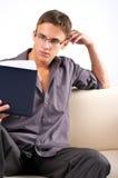 Livro de leitura do homem novo no sofá imagens de stock royalty free