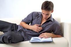 Livro de leitura do homem novo no sofá foto de stock