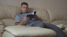 Livro de leitura do homem novo que senta-se no sofá em casa vídeos de arquivo