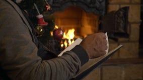 Livro de leitura do homem superior perto da chaminé e árvore de Natal na véspera do xmas vídeos de arquivo