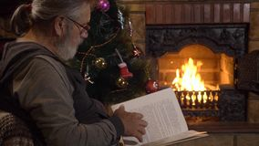Livro de leitura do homem superior perto da chaminé e árvore de Natal na véspera do xmas video estoque