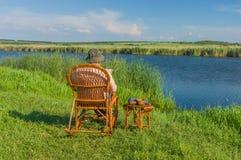 Livro de leitura do homem superior que senta-se na balançar-cadeira de vime fotografia de stock