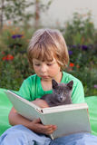 Livro de leitura do menino com o gatinho na jarda, criança com leitura do animal de estimação fotografia de stock