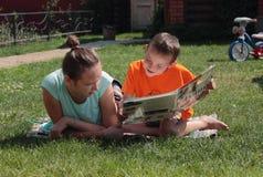 Livro de leitura do menino e da menina Fotos de Stock