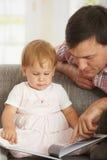 Livro de leitura do pai e do bebê no sofá Fotografia de Stock