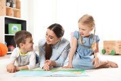 Livro de leitura do professor de jardim de infância às crianças Aprendizagem e jogo imagens de stock royalty free