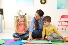 Livro de leitura do professor de jardim de infância às crianças Aprendizagem e jogo imagem de stock royalty free