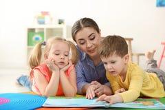 Livro de leitura do professor de jardim de infância às crianças Aprendizagem e jogo foto de stock