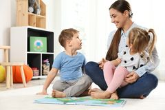 Livro de leitura do professor de jardim de infância às crianças Aprendizagem e jogo imagem de stock