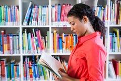 Livro de leitura do professor na biblioteca na escola fotos de stock