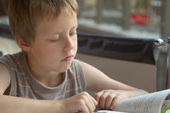 Livro de leitura do rapaz pequeno ao ar livre, na cidade Fotografia de Stock Royalty Free