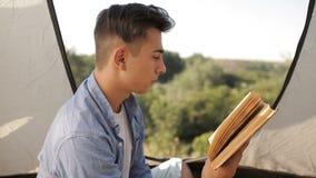Livro de leitura do turista do homem novo na barraca no local de acampamento na floresta video estoque