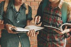 Livro de leitura de dois estudantes junto na sala da biblioteca na escola foto de stock