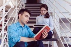 Livro de leitura dos estudantes junto na biblioteca Foto de Stock Royalty Free