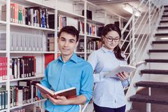 Livro de leitura dos estudantes junto na biblioteca Fotos de Stock Royalty Free