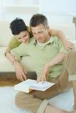 Livro de leitura dos pares em casa Fotografia de Stock Royalty Free