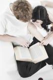 Livro de leitura dos pares em um sofá Foto de Stock Royalty Free