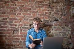 Livro de leitura esperto da estudante universitário do homem, assento com o laptop no espaço detrabalho fotos de stock royalty free