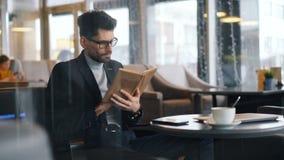 Livro de leitura esperto do empresário do homem no café centrado sobre a literatura vídeos de arquivo