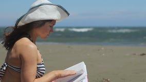 Livro de leitura fêmea moreno, apreciando o passatempo em férias de verão, tempestade no mar filme