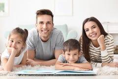 Livro de leitura feliz da família imagem de stock