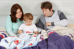Livro de leitura feliz da família Foto de Stock Royalty Free