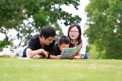 Livro de leitura feliz da família do latino imagens de stock